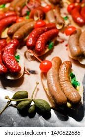 homemade sausages lie on a table decorated with tomatoes, capers and red pepper