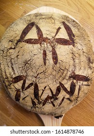 Homemade scored and halloween theme sourdough bread on a wooden bakeboard straight from the oven. Scoring is the technique term for slashing bread dough before baking with a sharp knife or razorblade.