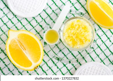 Homemade scrub (foot soak or bath salt) with lemon juice and zest, sea salt and olive oil. DIY beauty treatments and spa recipe. Top view, copy space