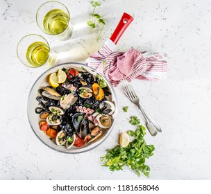 Homemade seafood Black pasta spaghetti with clams mussels octopus vongole in pan with white wine on marbled background.