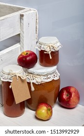 Homemade seasonal preparations. Beautifully packaged jars of apple jam. Covered with paper and tied with a cord. Nearby are fresh apples.