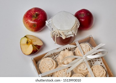 Homemade seasonal preparations. Beautifully packaged jars of apple jam. Covered with paper and tied with a cord. Next to fresh apples and apple marshmallow in the package.