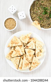 Homemade sesame pita chips with roasted eggplant dip or spread, baba ganoush in the Mediterranean cuisine on the side, photographed overhead with natural light