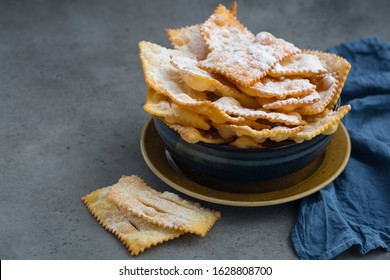 """Homemade """"sfrappole"""" or """"chiacchiere"""". Italian traditional sweet crisp pastry,  deep-fried and sprinkled with powdered sugar. Commonly eaten during Carnival and on Fat Thursday."""