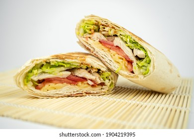 Homemade shawarma or burrito or pita or chicken roll with vegetables and sauce.
