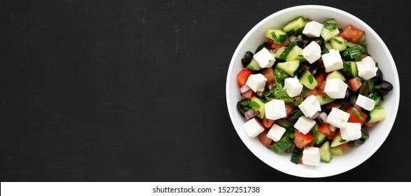 Homemade Shepherd's salad with cucumbers, feta and parsley in a white bowl on a black surface, top view. From above, overhead, flat lay. Space for text.
