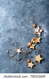 Homemade shortbread star shape sugar cookies different size with sugar powder on thread over blue texture surface. Christmas treat background. Top view with space