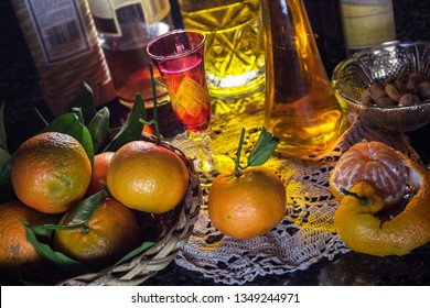 "homemade Sicilian mandarin liqueur called ""mandarinetto"", some mandarins in a basket and bottles of other liqueurs in the background. Alcohol drink"