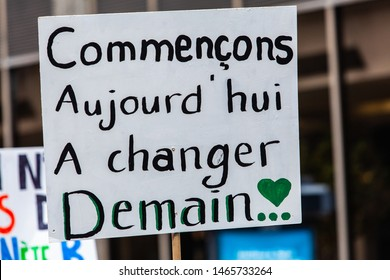 Homemade sign at environmental rally. A french poster, saying let's start today to change tomorrow, is seen close-up in the hands of ecofriendly activists during a street demonstration in Montreal
