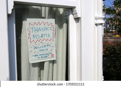Homemade sign in a house window thanking postmen and deliverymen during the coronavirus lockdown