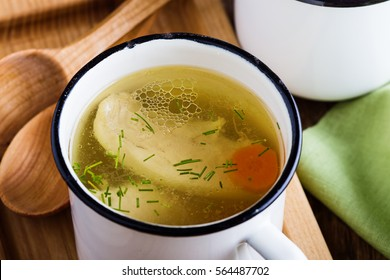 Homemade simple chicken soup in white mug on rustic wooden table, classic comfort food