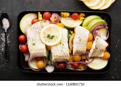 Homemade simple healthy. Farmer market vegetables white cod fish on a baking tray: zucchini, corn, purple onion, colored cherry tomatoes, micro greens, lemon. Top View