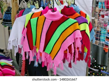 Homemade simple striped knitted warm ponchos are sold on  street. Snapshot style image