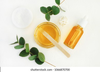 Homemade skin care and beauty treatment preparation with natural cosmetics honey and eucalyptus aroma oil. Yellow jars and bottle of facial mask top view with leaves white background.