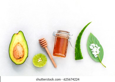 Homemade skin care and body scrub with natural ingredients fresh  avocado , leaves ,sea salt , lime and honey on marble background  with flat lay.