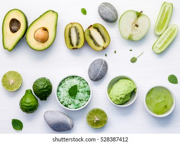 Homemade skin care and body scrubs with green natural ingredients aloe vera ,lime,cucumber ,aromatic salt ,green apple,mint ,kiwi and sage set up on white wooden background with flat lay.