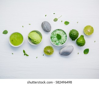 Homemade skin care and body scrubs with green natural ingredients aloe vera ,aromatic salt ,avocado scrub and spa stone set up on white shabby wooden background. Zen spa and oriental spa theme.