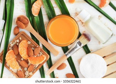 Homemade skin care cosmetic mask preparation with fragrant orange tangerine, almond and oat milk, top view with green fresh palm leaves, ingredients on wooden table.