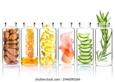 Hausgemachte Hautpflege mit natürlichen Zutaten und Kräuter in Glasflaschen einzeln auf weißem Hintergrund.