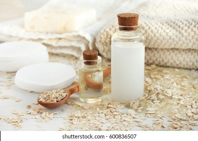 Homemade skincare cosmetic. Rice water and oat flakes facial cleanser. Bottle of cereal milk, grains, towels and cotton pads