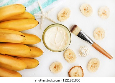 Homemade skincare mask with yummy mashed banana. Jar of cosmetic product prepared for home spa, ripe yellow fruit and slices, viewed above white table.