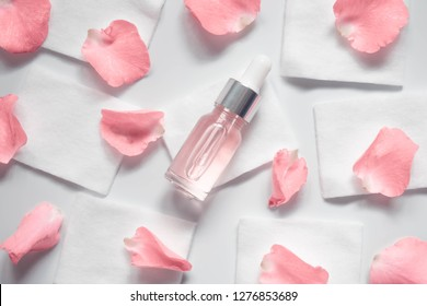 Homemade skincare natural rose water/essential oil product. Cosmetic glass bottle w/ dropper and pink rose on cotton pads for facial toner, cleansing, makeup remover, treat acne or moisturizing serum.