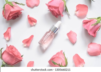 Homemade skincare natural rose water/essential oil product. Pink rose  and cosmetic glass bottle w/ dropper for moisturizing serum, facial toner, cleansing, makeup remover or treat acne. Flat layout.