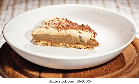 Homemade Slice of Banoffee Pie, served in a bowled plate on a wooden board.