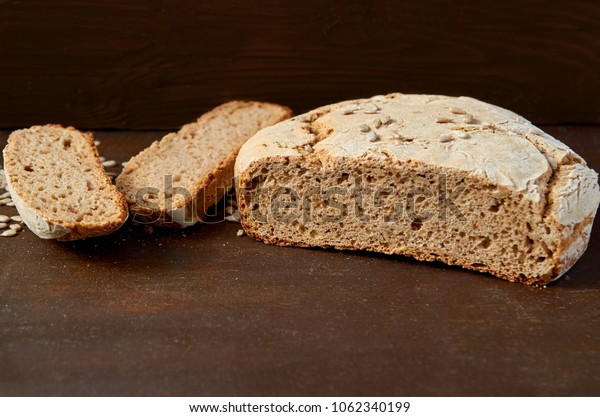 Homemade sliced appetizing fresh bread on the wooden background ready to eat. Just baked round bread on the brown table with free copy space. Side view