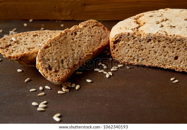 Homemade sliced fresh bread with sunflower seeds on the wooden background ready to eat. Just baked tasty bread on the brown table with free copy space. Side view