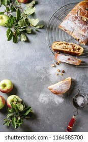 Homemade sliced puff pastry apple strudel pie on cooling rack served with ripe fresh apples, branches and sugar powder over grey texture background. Flat lay, space