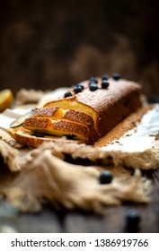 Homemade sliced tasty rectangular baked lemon cake with blueberries on paper and sackcloth stand on rustic table with bottle of spices, cup of berries, lemons, towel, spoons, strainer, knife
