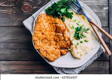 Homemade Sliced Wiener Chicken Schnitzel with herb and mashed potatoes on plate on wooden table background. Healthy food. Top view