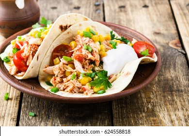 Homemade slow cooker chicken taco with corn served on rustic ceramic plate on wooden table, mexican style