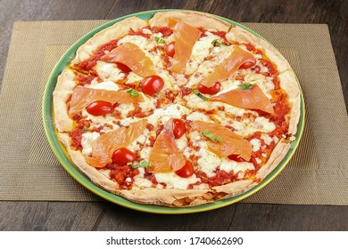 Homemade Smoked Salmon Pizza with mozzarella cheese, mascarpone, basil, cherry tomatoes on wooden table