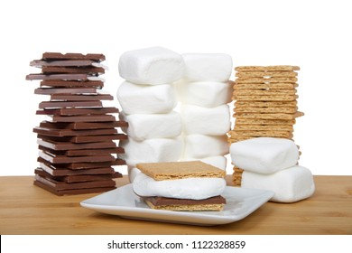 Homemade s'more on a square plate with stacks of graham crackers, chocolate and marshmallows on a wood table, isolated background on white.