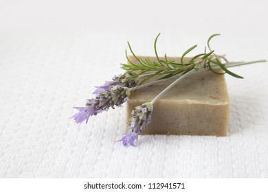Homemade soap with lavender and rosemary over white towel background