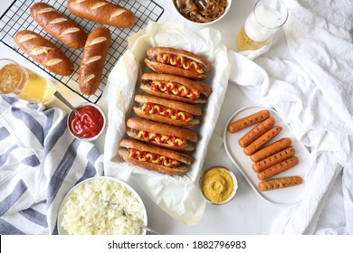 Homemade soft pretzels buns filled with hot dogs - ketchup and mustard against white background with Sauerkraut and fried onion - Fast food, German food concept, oktoberfest background. Copy space