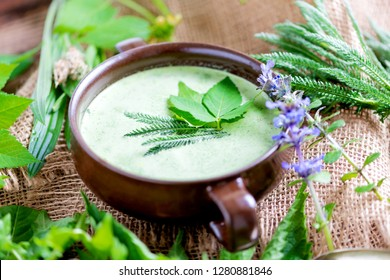 Homemade soup made from local wild herbs on a wooden plate (meadow herbs)