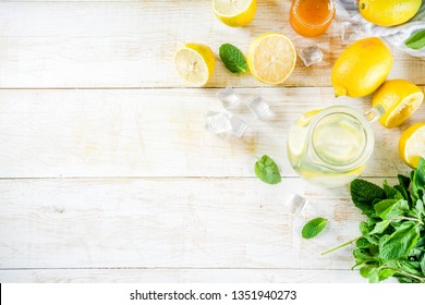 Homemade sour cocktail lemonade, with fresh lemons, mint and honey, white wooden background copy space