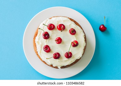 Homemade sour cream cake with cream cheese frosting decorated with fresh ripe cherries on a light blue background. Top view.