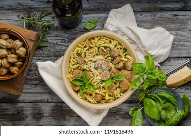 Homemade spaetzle, barbecue sausage and fresh cheese, herbs on rustic wood board, food photography