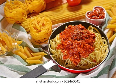 Homemade spaghetti bolognese in frying pan. Decorated with tomato sauce in the love ceramic cup and ingredients on background. Concept about love and relationship.