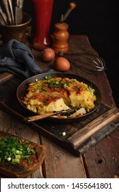 Homemade Spanish tortilla in a frying pan on a wooden vintage rustic table. Copy space
