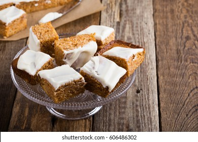 Homemade spiced pumpkin cake with cream cheese frosting sliced into squares, served on glass stand on rustic wooden table