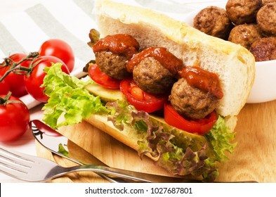 Homemade spicy meatball sub sandwich with marinara sauce and tomatoes