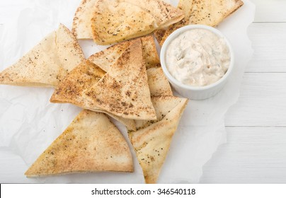 homemade spicy  pita chips made from pita bread with olive oil and spices on white paper with Greek yogurt dipping sauce with herbs