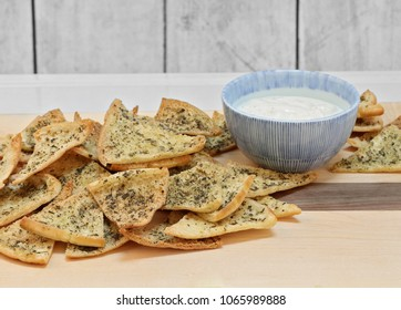 Homemade spicy pita chips on a cutting board with a bowl of dip.