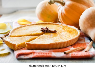 Homemade spicy pumpkin pie with cinnamon on a table with pumpkings at background