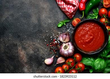 Sauce tomate épicée maison avec ingrédients pour la fabrication sur fond noir, pierre ou béton. Vue de dessus avec espace de copie.